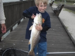 Alex, Board Member, Bob Brumby\'s grandson at the hatchery fish pond,